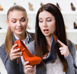 Salesperson offers high heeled shoes for the female customer