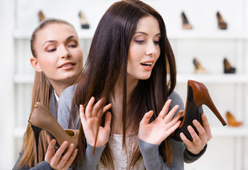 Shop assistant offers heeled shoes for the female customer
