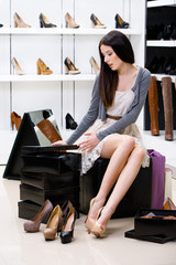 Woman sitting on the chair and trying on pumps