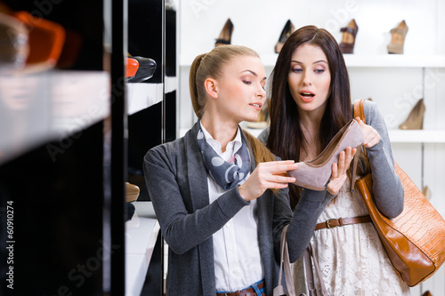 Salesperson shows heeled shoes to the customer