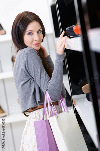 Woman choosing a pair of shoes in shopping center