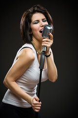 Half-length portrait of female rock musician with microphone