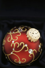 Elegant christmas bauble in red and gold on night blue satin