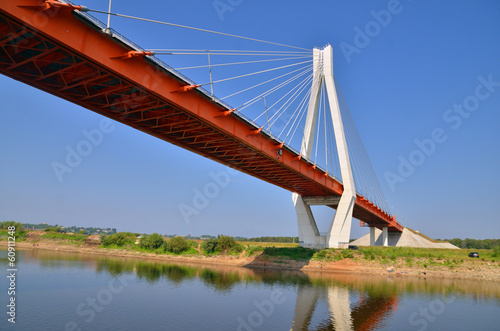 a big red and white bridge through the river Oka