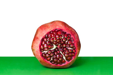 Open Pomegranate with seeds on white and green background