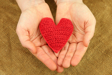 Knitting heart in the hands