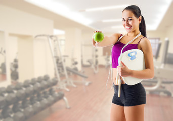 Sporty girl with apple and scales at fitness club
