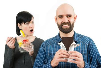 Frau schaut vorwurfsvoll zu Schokolade essendem Mann