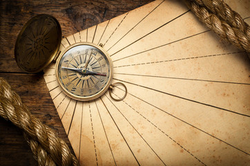Old compass and rope on vintage paper.