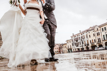 Newlyweds walking under the rain