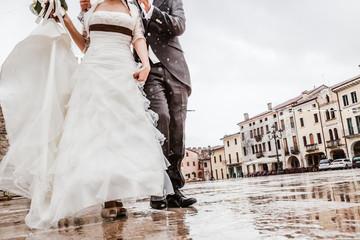 Newlyweds walking under the rain