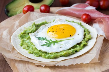 Breakfast with fried egg and sauce of avocado on grilled flour