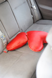 Two red pillows in the shape of heart on the back seat of a car