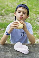 Niño que está disfrutando de picnic come un sandwich
