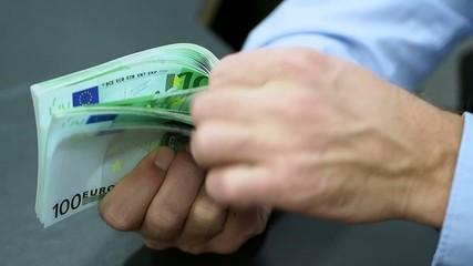 Bank clerk counting 100-bills of Euros