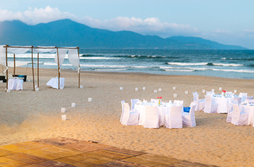 White tables served for supper on beach.