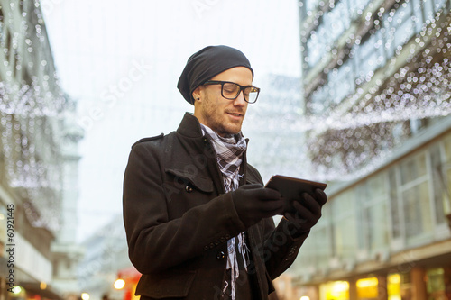 Urban man holdin tablet computer on street