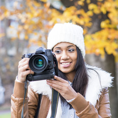 Portrait of smiling girl with bonnet and camera, autumn.