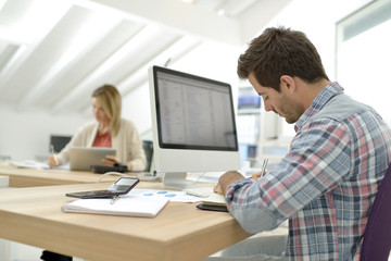 Back view of office worker sitting at desk