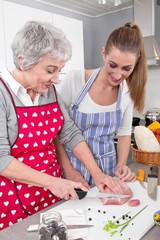 Mutter und Tochter in der Küche schneiden Fleisch