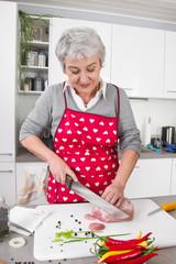 Frau bereitet in der Küche einen Schweinebraten zu