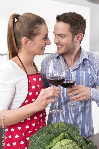 Liebespaar in der Küche trinkt gemeinsam Wein