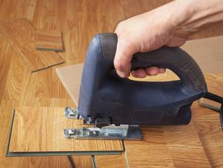 Master using an electric jigsaw saws laminated panel