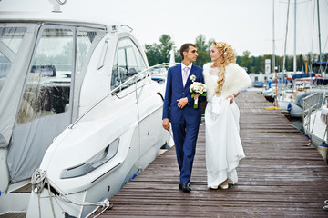 Romantic bride and groom go to the pier with yachts boats