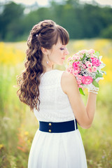 portrait of a girl in a white dress with a bouquet of flowers in