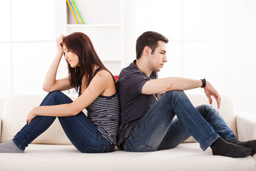 Young couple sittin back to back on the sofa,having relationship