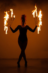 Attractive female artist holding and juggling using flaming fan