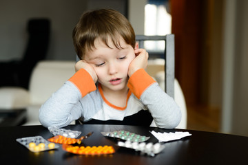 worried 4 year old boy sitting at the table with medications