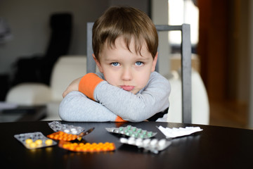sad preschooler sitting at the table with pills