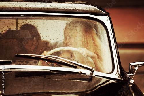 Young woman driving retro car in the rain