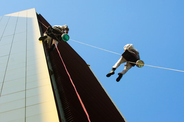 Two men hanging high on a rope while working