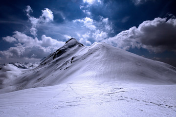 Snowy  and shiny mountain top with footsteps in the foreground