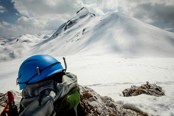Helmet and backpack on a rock with white mountain in background