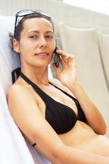 Frau telefoniert am Schwimmbad