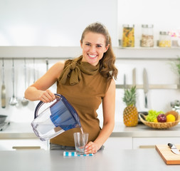 Happy young housewife pouring water into glass from water filter