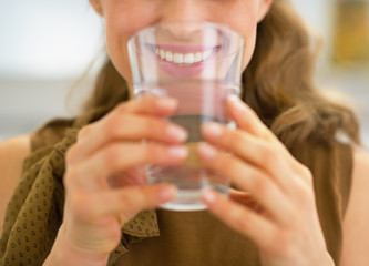 Closeup on young housewife drinking water