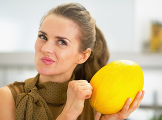 Happy young housewife checking ripeness of melon