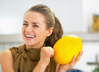 Smiling young housewife checking ripeness of melon