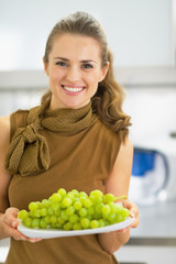 Happy young woman showing branch of grapes