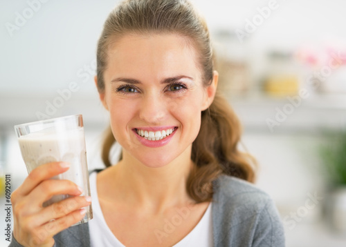 Leinwandbild Motiv Portrait of happy young woman drinking smoothie in kitchen