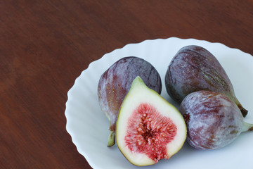 4 fresh figs on white plate on table