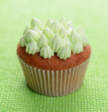 Tasty cupcake with butter cream, on color background