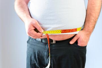 Übergewichtiger Mann misst seinen Bauchumfang