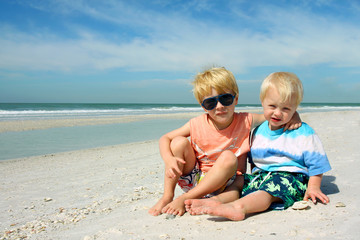 Two Young Children Sitting on Beautiful Beach