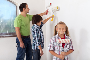 Kids and their father painting a room