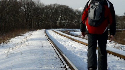 man with a backpack walking on snow-covered rail